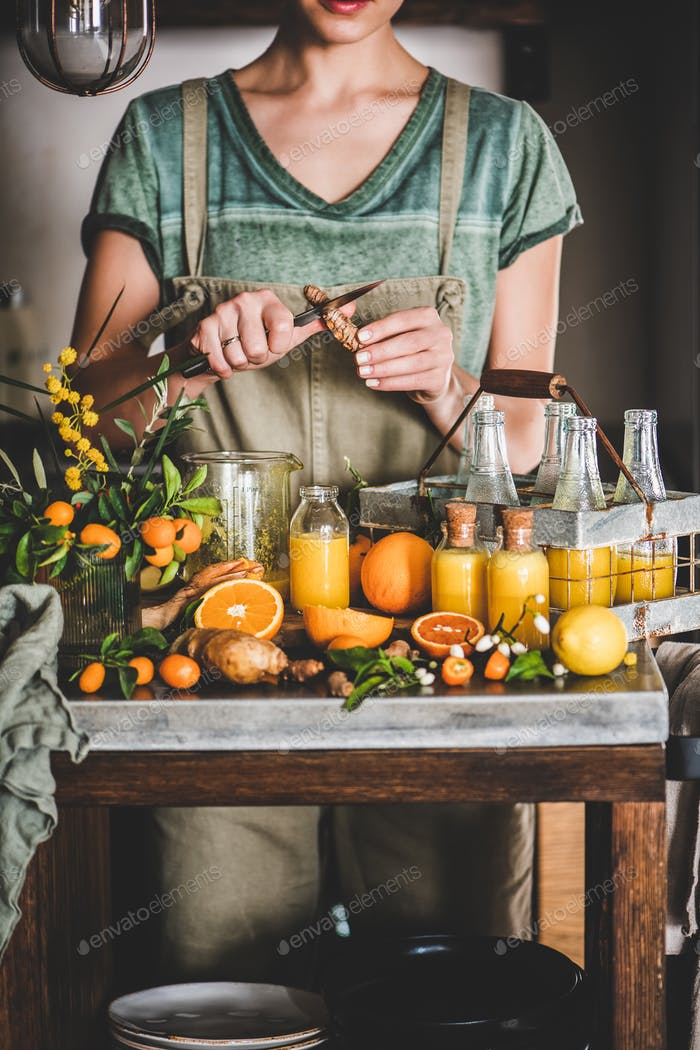Young woman making fruit immune boosting drink to resist virus