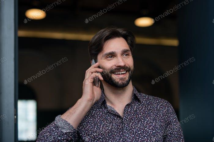 Portrait of young businessman standing indoors, using smarpthone