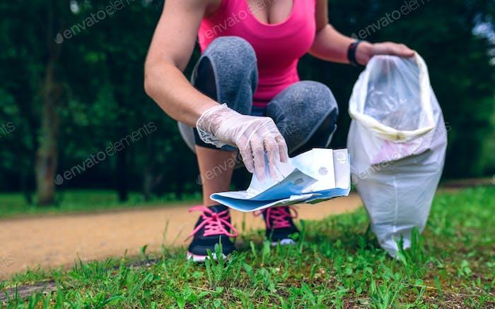 Girl picking up trash doing plogging