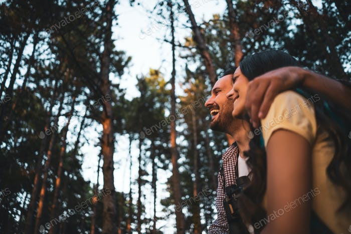 Happy couple is hiking in forest