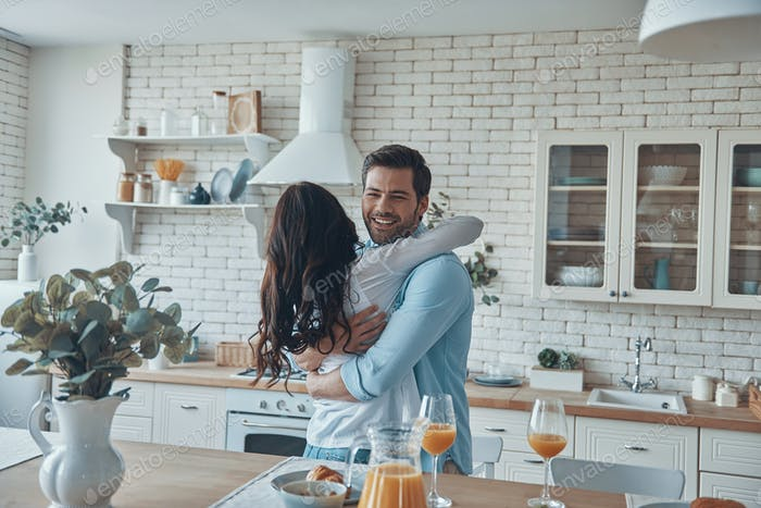 Beautiful young couple embracing while spending time in the domestic kitchen