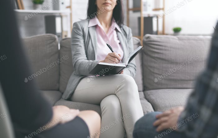 Family psychologist listening to married couple at personal meeting