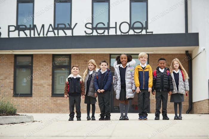 Primary school kids standing in front of their school looking to camera, full length, low angle