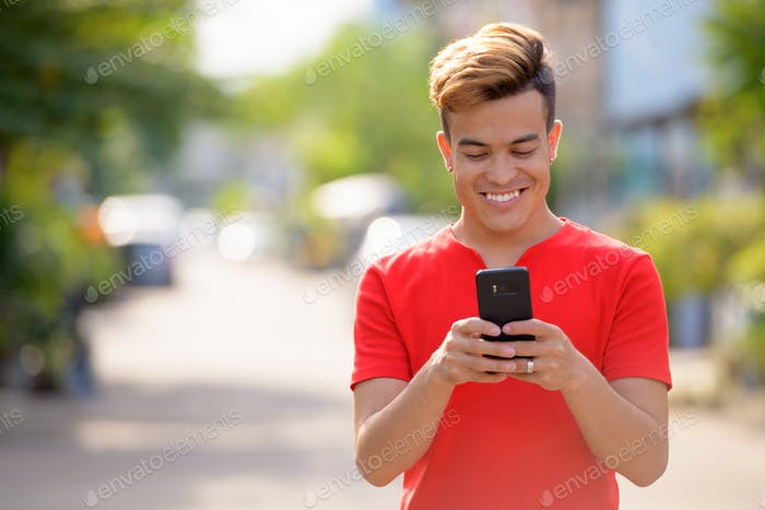 Happy young Asian man using phone in the streets outdoors