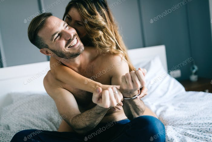 Back view of woman in black panties holding her bra while man is lying on bed