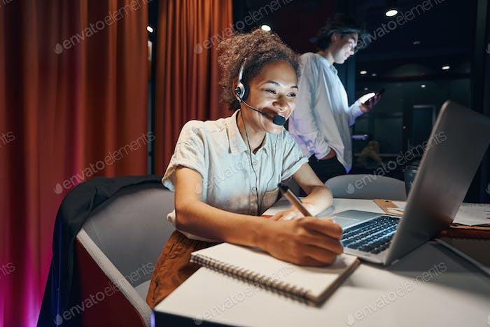 American woman working on laptop in cabinet
