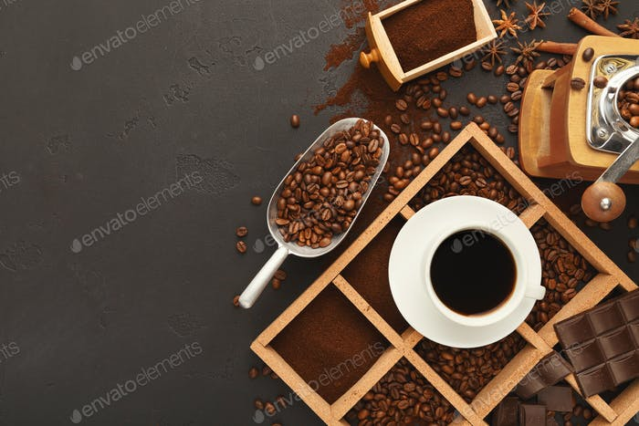 Top view on scattered coffee beans and spices, background with c