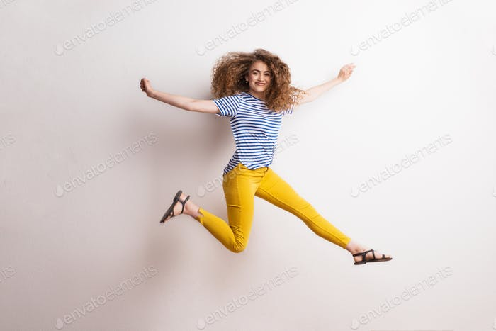 Young beautiful joyful woman with long curly hair in studio, jumping.