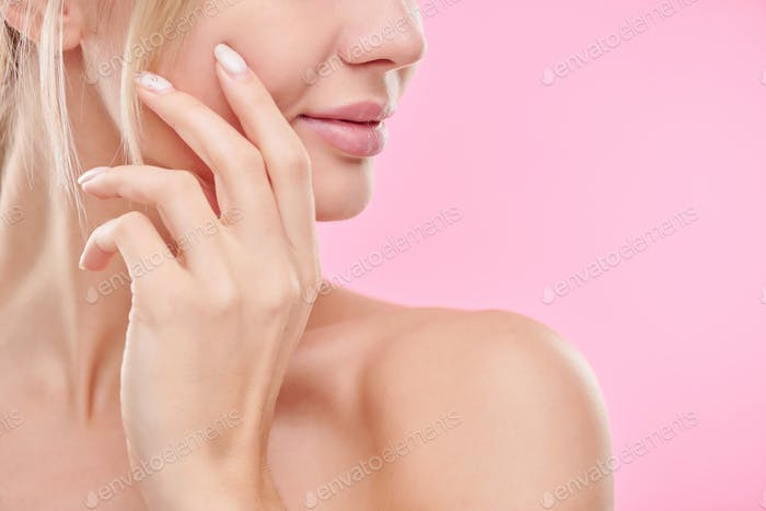 Hand of young healthy woman touching her face while taking care of skin