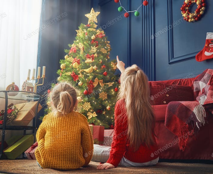 sisters near Christmas tree
