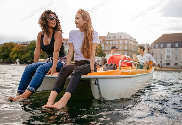 Teenage friends relaxing on pedal boat in lake