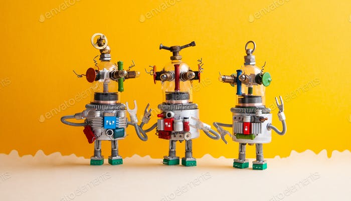 Funny glass headed ufo robots on a fantastic landscape. Three humanoid toy robots communicate.