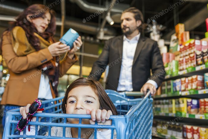 Girl sitting in cart with parents shopping at supermarket