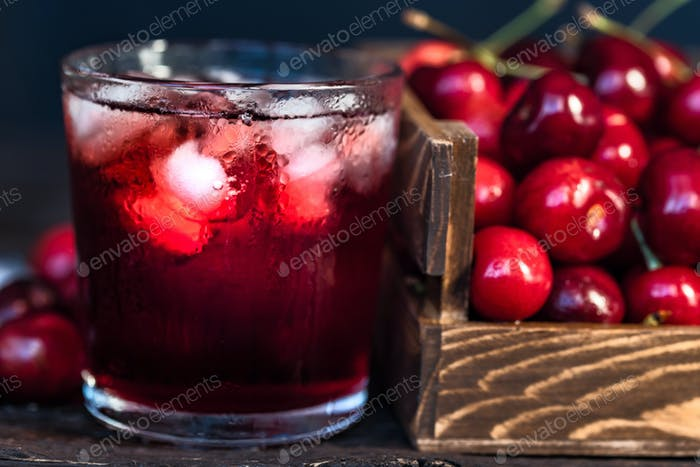 Fresh cherries in a wooden box, ice, cherry juice