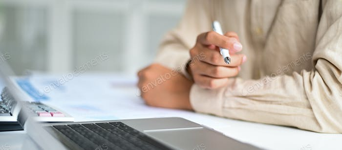 Cropped shot of Businessman holding pen in hand on desk,Business concepts.