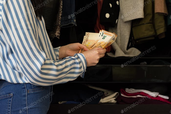 Young brunette woman Counting the money saved