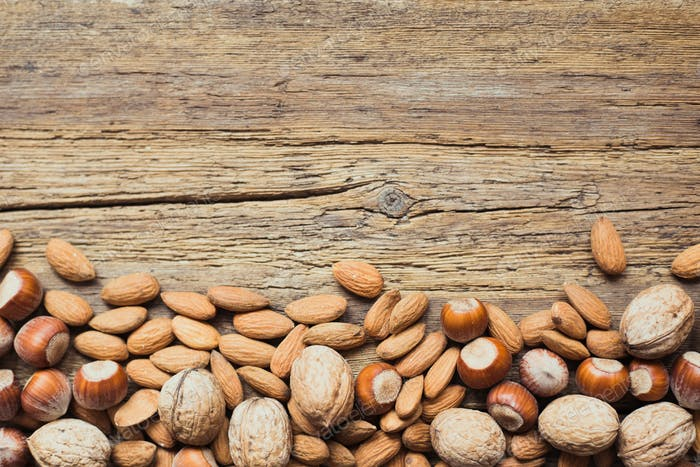 Assorted nuts in a wooden background