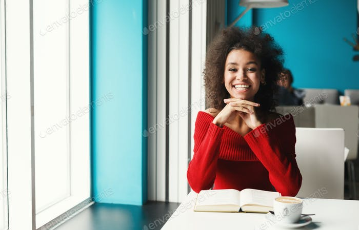Happy black girl at cafe reading a book