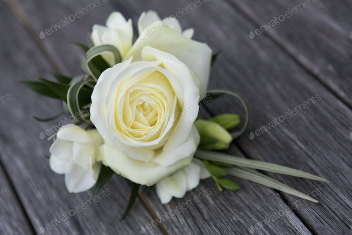 A boutonniere, button hole flower, a cream rose.