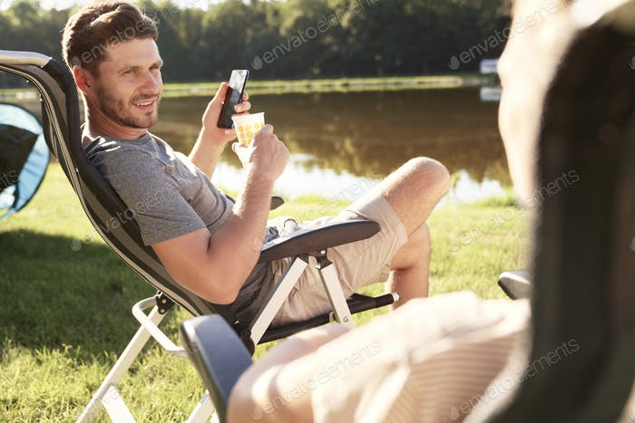 Men chilling on camping by the lake