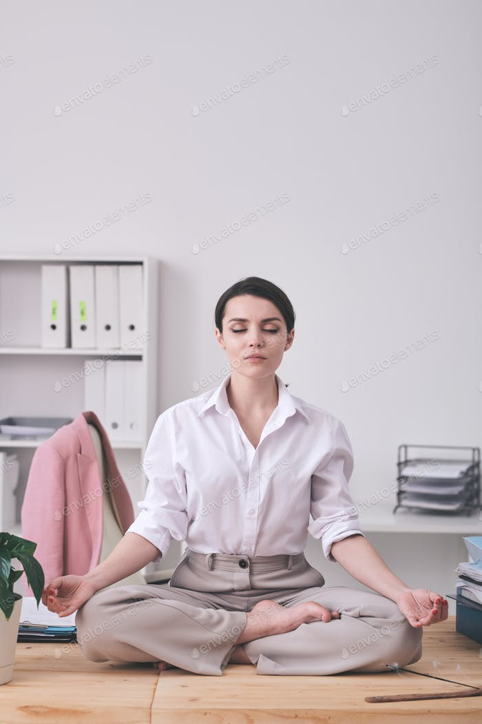 Calm businesswoman meditating in office