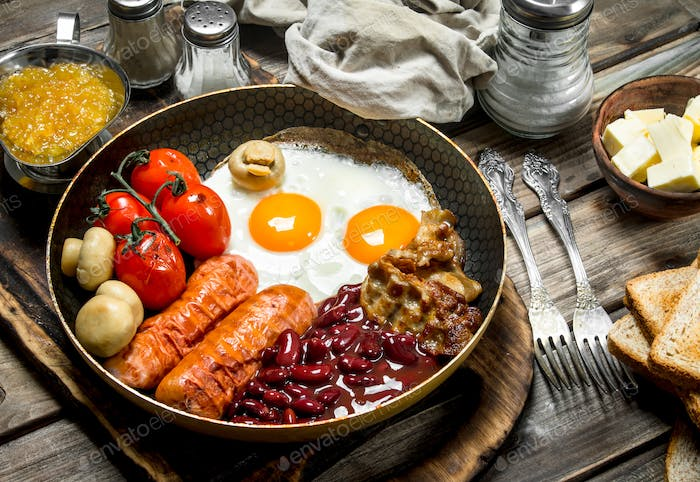 English breakfast.Fried eggs with sausages, bacon and red canned beans.