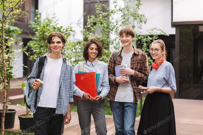 Group of young smiling students standing with books and folders in hands