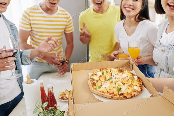 Party host opening box of pizza