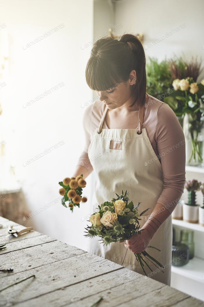 Florist making flower arrangements at a bench in her shop