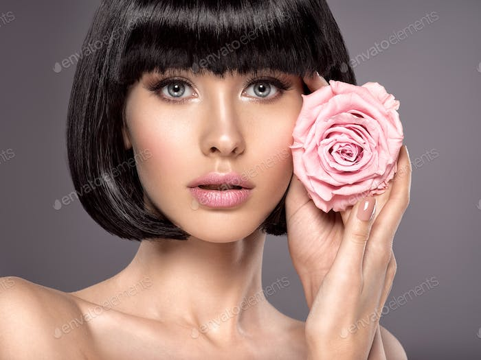 Woman with beauty short black hair holding rose flower.