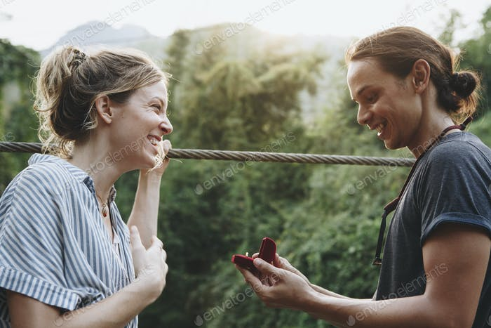 Man proposing to his happy girlfriend outdoors love and marriage concept