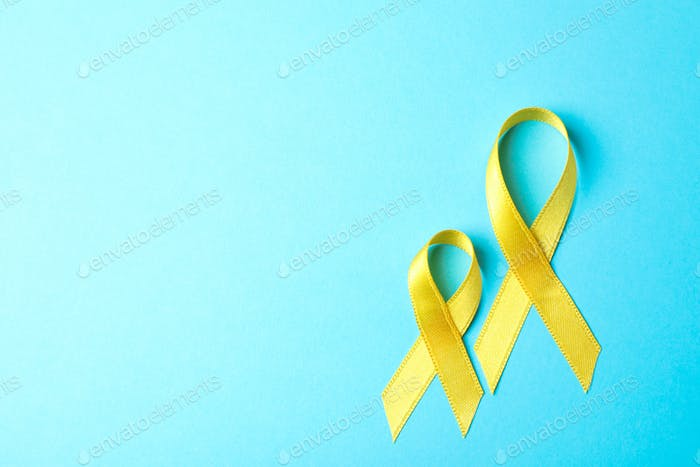 Yellow awareness ribbons on blue background, space for text.