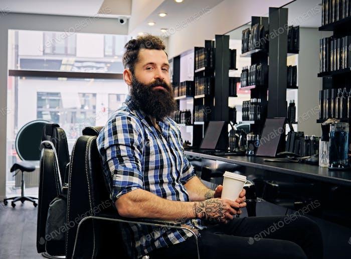 Male drinks coffee in a hairdresser's salon.