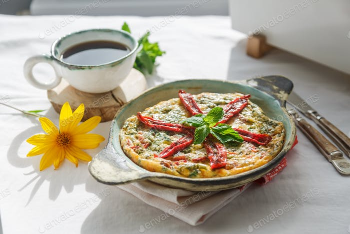 Traditional fritatta with dry tomatoes in a cast iron pan. White background, copy space