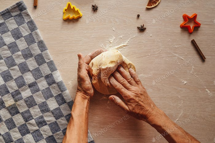 hands knead the dough on table.