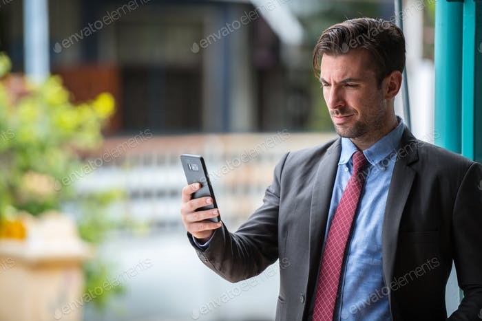 Young handsome Hispanic businessman using phone outdoors