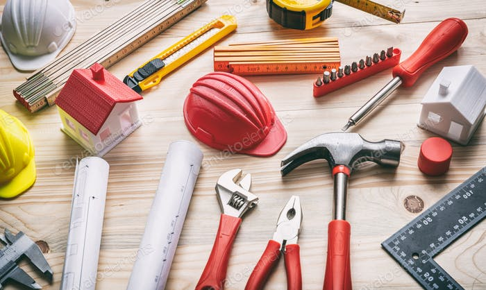 Tools, hardhats and project plans on wooden desk