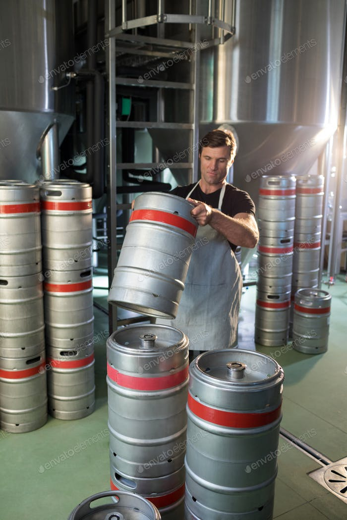 Male worker arranging kegs