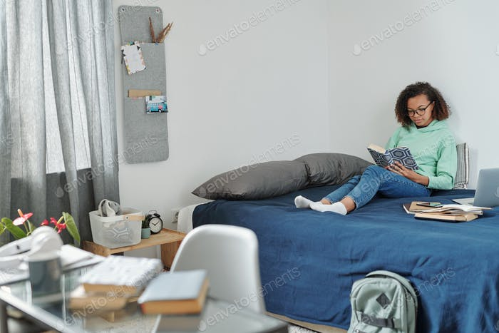 Young pretty diligent student with open book preparing home assignment