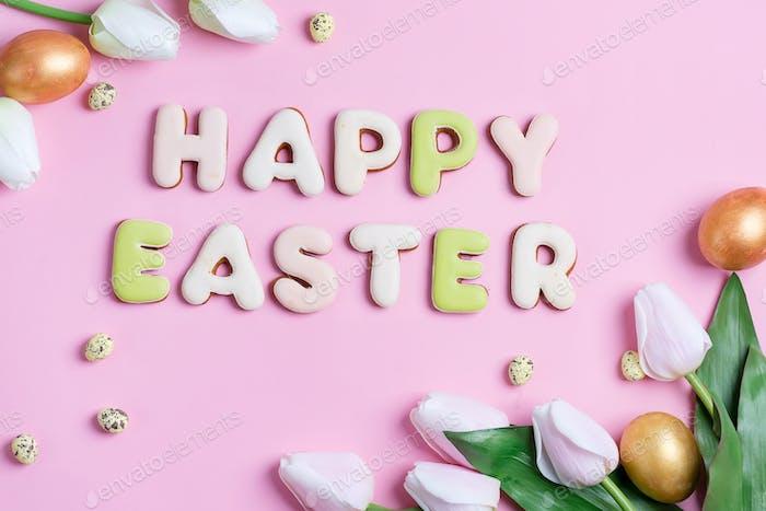 Glückliche Osterkarte aus handgefertigen bemalten Eiern, Tulpen Blumen und gebackenen Buchstaben Kekse auf einem rosa