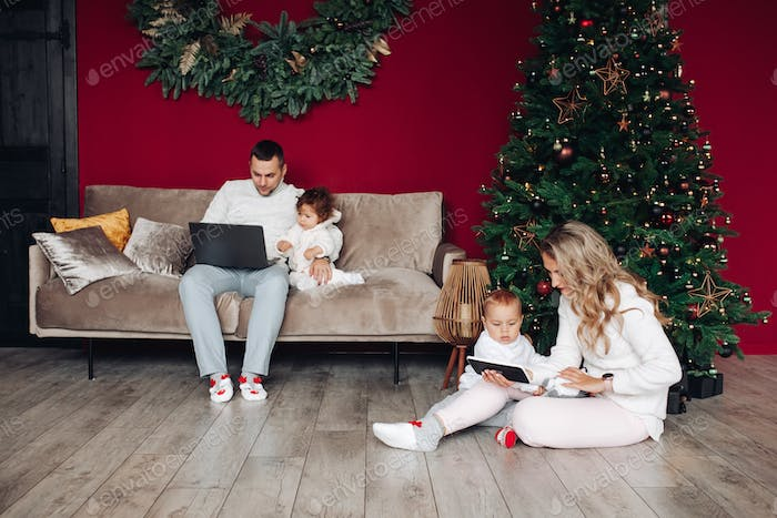Family using devices with children at Christmas