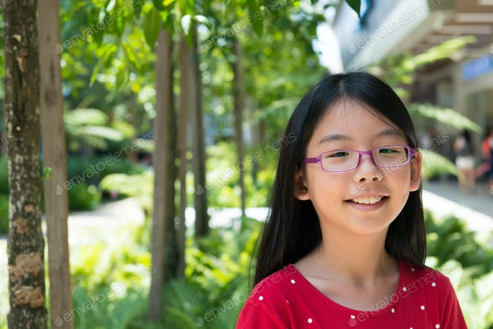 Cute Asian Chinese girl with glasses in park