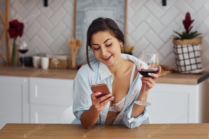 Woman in light wear is on the kitchen with drink of wine