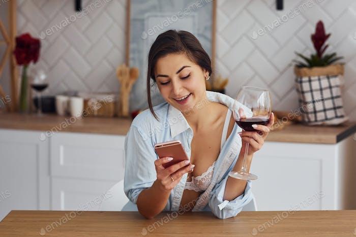 Frau in leichter Kleidung ist in der Küche mit einem Getränk Wein
