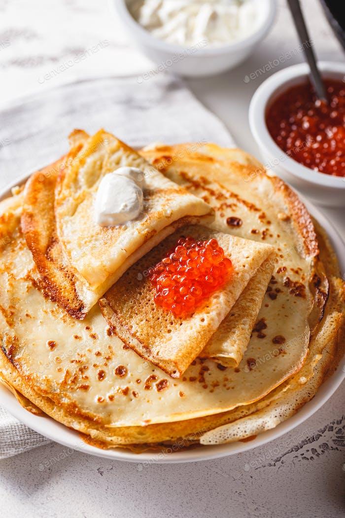 Stapel russischer Pfannkuchen blini mit rotem Kaviar, frische saure Sahne