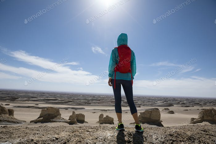 Successful woman trail runner on sand desert dunes
