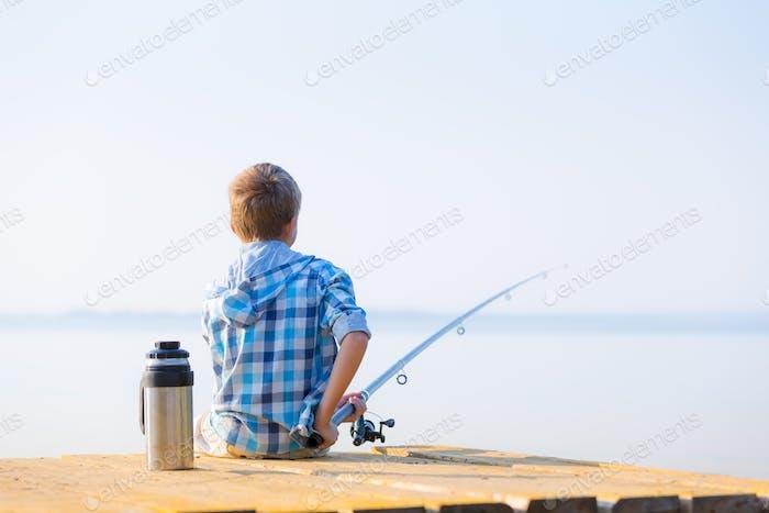 Boy in blue shirt sit on a pie