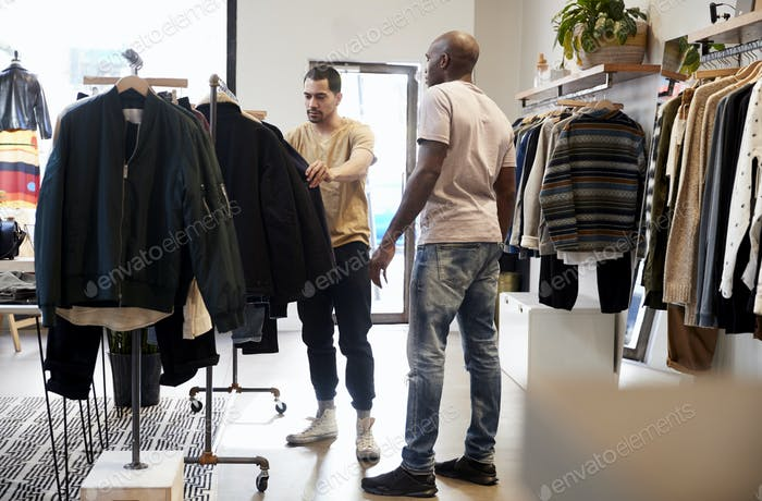 Shop assistant helping customer in a menÕs clothes shop