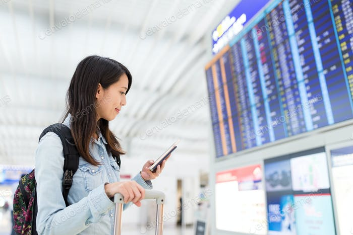 Mujer comprobando vuelo en el teléfono móvil en el aeropuerto