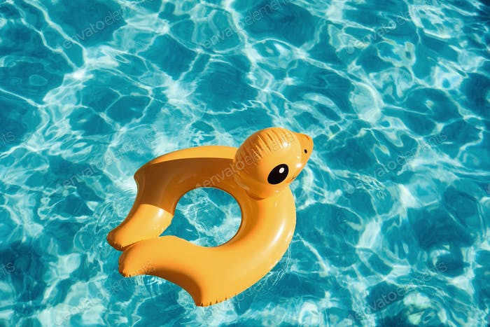 Top view of yellow duck toy for swimming in the pool at daytime